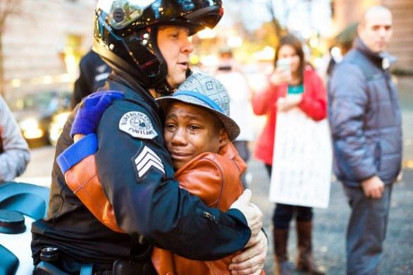 Tra le manifestazioni e la violenza, tra gli incendi e gli scontri con la polizia, le macchine distrutte e i gas lacrimogeni, i cartelli di protesta per sfogare la rabbia e la confusione che fa perdere i confini di quello che accade, un barlume di speranza si è acceso anche in una città nel caos come Ferguson. Il fotografo Jonny Nguyen ha scattato una delle foto più belle, forti ed emozionanti viste nelle ultime settimane: l'abbraccio tra un giovanissimo manifestante pacifista e un poliziotto.