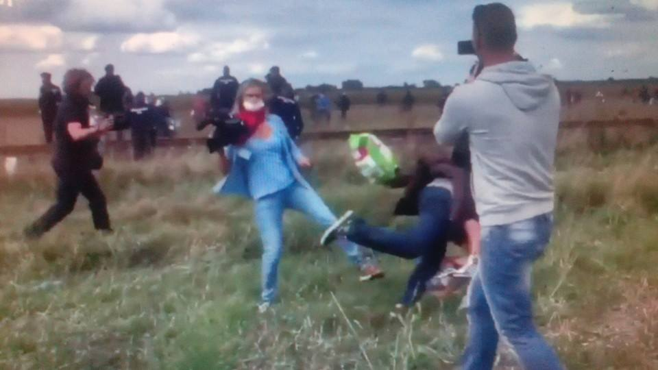 giornalista  reporter sgambetto rifugiato con figlio