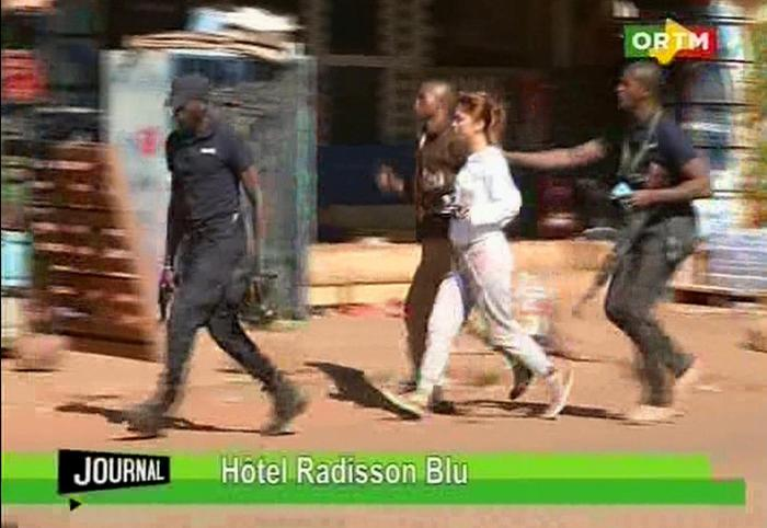 """In this TV image taken from Mali TV ORTM, a woman is led away by security personnel from the Radisson Blu Hotel  hotel in Bamako, Mali, Friday Nov. 20, 2015.  Men shouting """"God is great"""" and armed with guns and throwing grenades stormed into the Radisson Blu Hotel in Mali's capital Friday morning. (Mali TV ORTM,  AP) MALI OUT"""